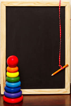 empty blackboard in a wooden frame with a pencil on a string next to a colorful  pyramid. photo