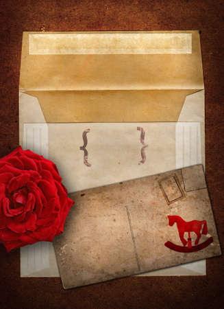 grunge envelop and card set with rocking horse design and red rose on copy space photo