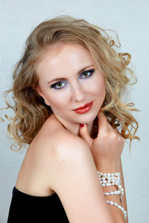beautiful blond woman with curly hair and dark evening make-up wearing corset and pearls photo