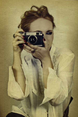young woman in white shirt taking picture with vintage film camera on grunge background  photo