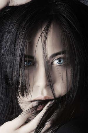loose hair: Foto di moda della bella donna giovane con i capelli neri sul suo viso, toccando le labbra - basso-chiave illuminazione.