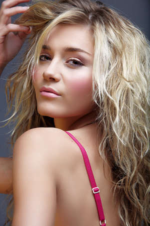 looking over shoulder: beautiful blond young woman with curly hair and natural make-up - naturally perfect skin texture