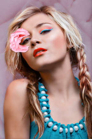 beautiful woman with pink rose, bright liner on her eyes and fashionably braided blond hair. photo