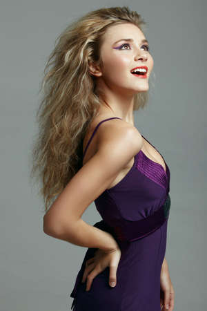 happy beautiful young woman with long blond hair wearing a purple evening dress. Stock Photo - 8215939