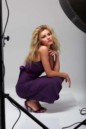 photo shoot: beautiful professional female model in purple dress resting between shots in a photographic studio shoot set-up