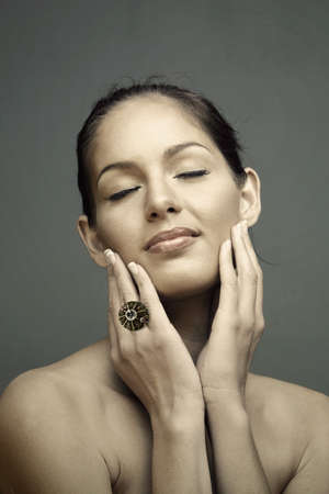 closed eyes beautiful woman wearing and classic natural make-up touching her face, wearing a large ring Stock Photo - 8215930