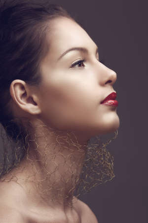 beautiful brunette woman with classic red lips and golden net around her neck in sepia cross-processed effect photo