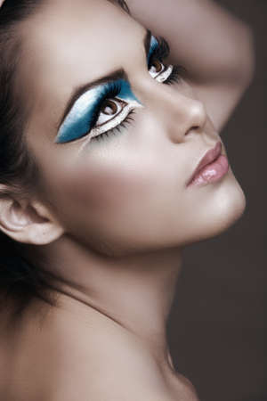 Beautiful brunette woman with cat eyes make-up in bright blue and white.