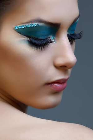 false eyelashes: Beautiful brunette woman with cat eyes make-up in bright blue and white.