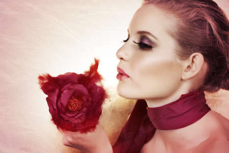 beautiful woman with red feather rose and bright make-up on pink background with copy space. photo