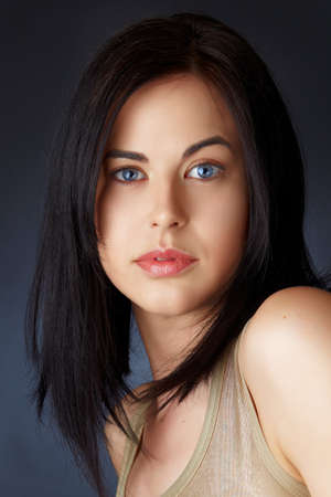 beautiful young woman with blue eyes and dark hair in structured bob haircut.