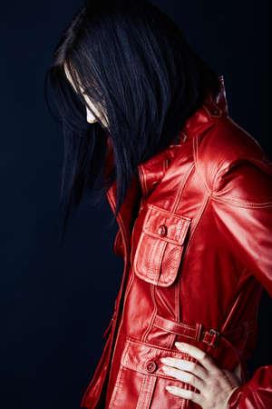 chaqueta de cuero: joven y bella mujer con cabello oscuro en bob estructurado que llevaba una chaqueta de cuero rojo sobre fondo oscuro de estudio.