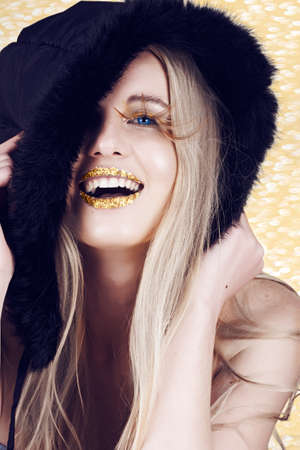 beautiful blond woman with gold make-up and long feather lashes, wearing winter hat laughing in a spirit of the New Year. photo