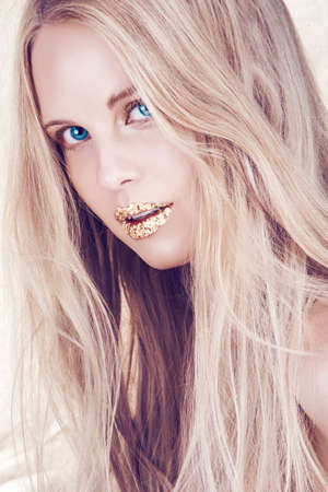 beautiful woman with long blond hair and blue eyes with artistic gold leaf lips photo