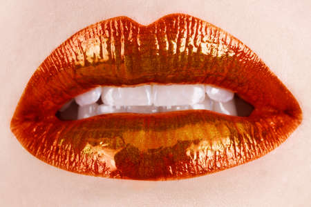 macro of woman's lips with orange and metallic lipstick Stock Photo - 8215997