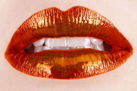 macro of woman's lips with orange and metallic lipstick Stock Photo - 8215997