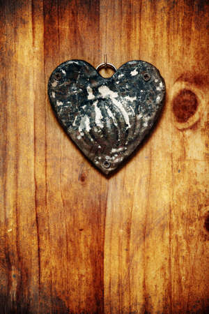 notecard: grunge metal heart ornament on a rustic wood background. Stock Photo