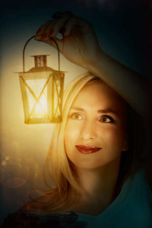 young beautiful woman hanging a lantern with bright light photo