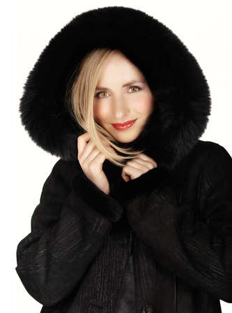 young beautiful woman happy in her winter black fur coat on white background. photo