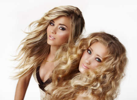 hair curl: two beautiful blond woman sisters with styled blond hair blowing ion the wind on white background - not isolated. Stock Photo