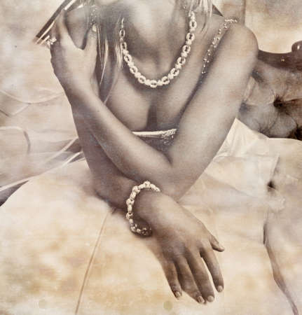 closeup of a beautiful bride in revealing dress wearing silver necklace on grunge stained background