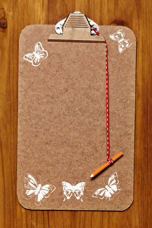 empty wooden clipboard with butterflies stencils in white on wooden panel and orange pencil. photo