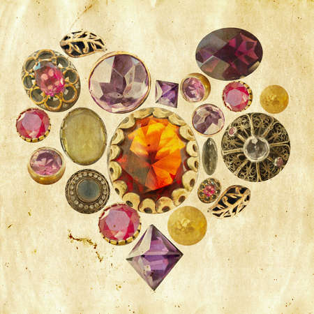 gems and precious stones arranged in heart shape on grunge paper background photo