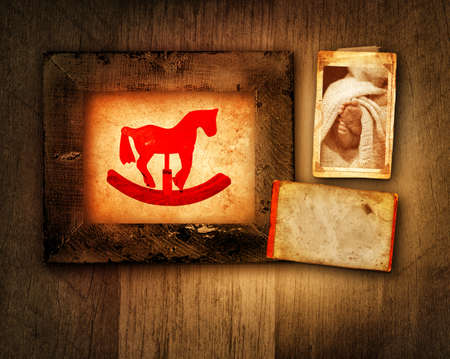 grunge frame with rocking horse and a picture of baby feet on textured wood background with copy space photo