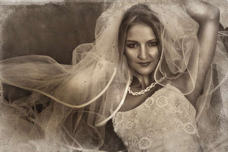 the happy bride: beautiful bride with large veil and silk wedding dress on grunge background with texture detail. Stock Photo
