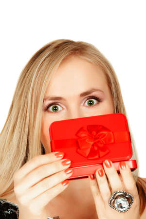 young blond woman opens a red gift box and her eyes are big with surprise - can be extended for copyspace photo