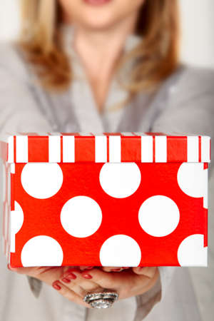 stipe: woman holding a gift red box with white polka dot and stipe - focus on the box. Stock Photo