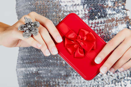 silver dress: red gift box with satin bow in hands of a young woman wearing a large flower ring and a silver sequin dress . Stock Photo