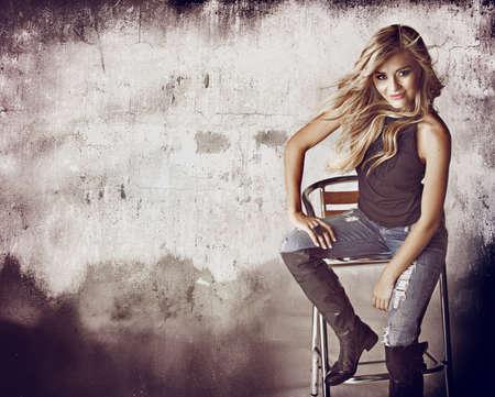 rocker girl: hermosa mujer rubia en pantalones vaqueros rasgados y pelo soplando en el viento sentado contra la pared de grunge con espacio para texto. Foto de archivo