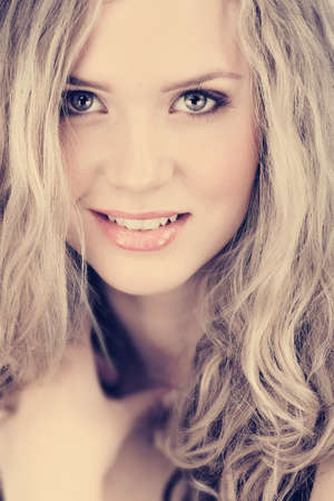 beautiful young woman with long curly blond hair and natural make-up smiling happily with cross process effect from 16 Bit RAW Stock Photo - 8744657