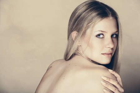 blonde yeux bleus: belle jeune femme aux longs cheveux blonds saine et naturellement m�me texture de la peau sur le mur texture grunge avec copie espace.
