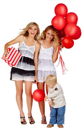 two beautiful girls laughing with red balloons and gift box and little boy playing next to them. photo