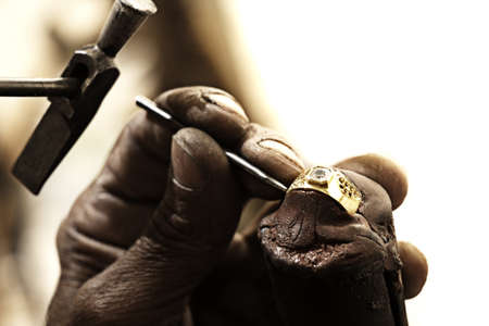 unpolished: hardworking Goldsmith working on an unfinished 22 carat gold ring with his aged hands Stock Photo