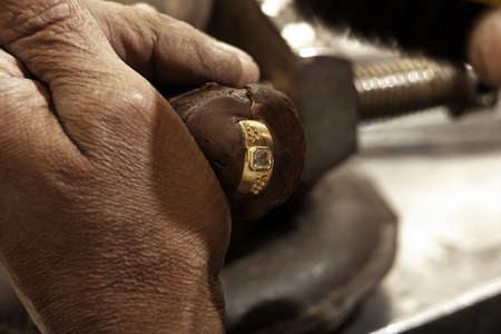 smith: hardworking Goldsmith working on an unfinished 22 carat gold ring with his aged hands Stock Photo