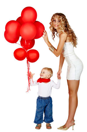 beautiful young woman with long curly hair wearing party sequin minidress and gold shoes playing with a little boy in jeans holding bunch of red balloons. photo
