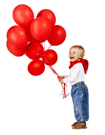cute little boy in white shirt, jeans and red scarf laughing as he holds a bunch of red balloons. photo