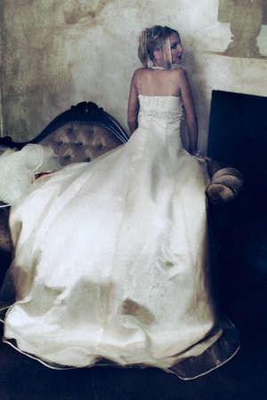 beautiful blond bride in long wedding dress resting on grunge vintage background with stains and spots photo