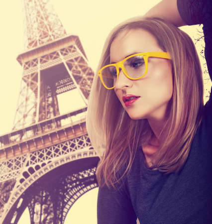 beautiful young blond woman wearing fashionable yellow glasses against Eiffel Tower in Paris with cross-processed effect. photo