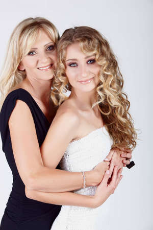 beautiful real couple mother in her 40s and teenage daughter wearing evening wear and make-up in studio Stock Photo - 8867217