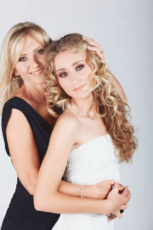 beautiful real couple mother in her 40s and teenage daughter wearing evening wear and make-up in studio Stock Photo - 8867215