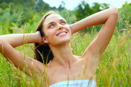 happy beautiful young teenage woman with long brunette hair sitting in tall green grass on the farm in bright sunshine - green cast from the grass Stock Photo - 8867223