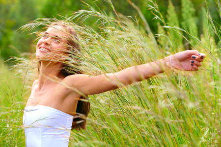 happy beautiful young teenage woman with long brunette hair standing in tall green grass on the farm in bright sunshine with her arms stretched photo