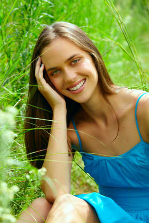 happy beautiful young teenage woman with long brunette hair sitting in tall green grass on the farm in bright sunshine - green cast from the grass photo