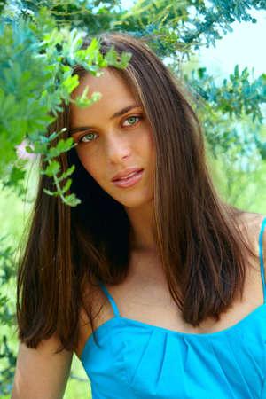 portrait of happy beautiful young teenage woman with long brunette hair outdoors on green nature background Stock Photo - 8867226