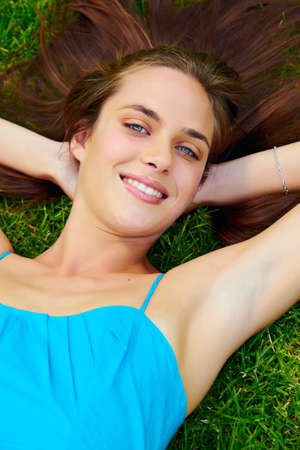 happy beautiful young teenage woman with long brunette hair lying and dreaming on green grass on the farm in bright sunshine photo