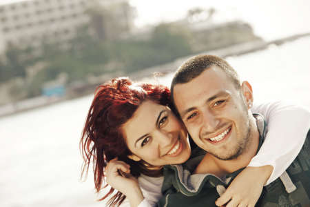 turkish man: young turkish happy couple on the beach embracing and laughing laughing on the sea background, focus on the man